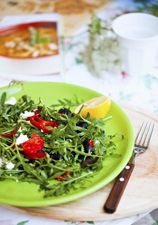 arugola: Rocket salad with olives, goats cheese and peppers on a light green plate LANG_EVOIMAGES
