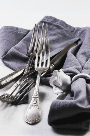 silver cutlery: Old silver cutlery with a grey napkin on a white table cloth