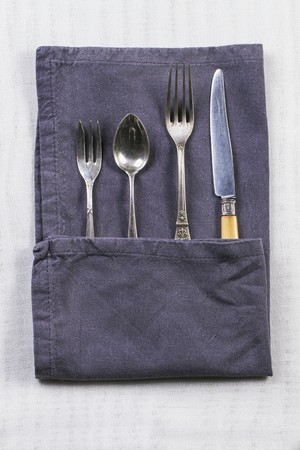 silver cutlery: Old silver cutlery in a grey napkin on a white table cloth LANG_EVOIMAGES