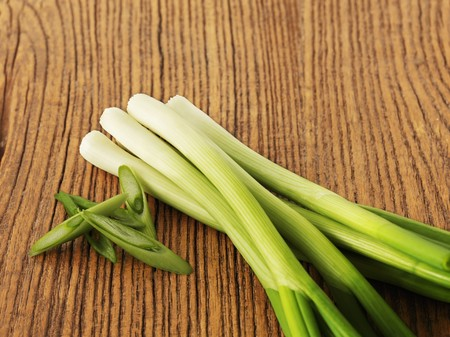spring onions: Spring onions, partially sliced, on a wooden surface