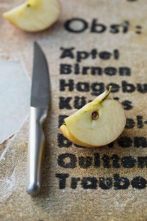 quartered: An apple quarter next to a knife