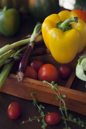 spring onions: A yellow pepper, red spring onions, cherry tomatoes and herbs in a wooden crate