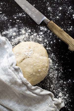 pizza dough: A ball of pizza dough with flour, a cloth and a knife