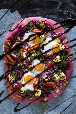 arugola: Beetroot pizza dough with broccolini, red onions, tomatoes, goats cheese, rocket, cheese, fired eggs and balsamic cream LANG_EVOIMAGES