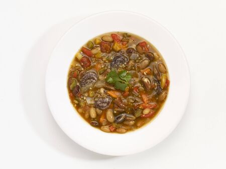 A bowl of bean soup in front of a white background (seen from above) LANG_EVOIMAGES