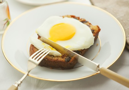 Poached egg on banana bread cut with a knife and fiork