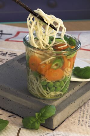 go inside: Asian noodle soup with peas, carrots and basil in a glass