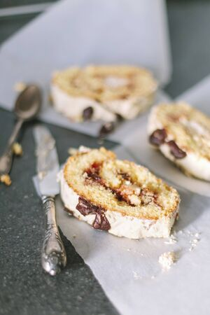 Biscuity roll with fruit and chocolate filling on a white parchment