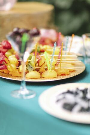 A plate of fruit skewers on a garden table