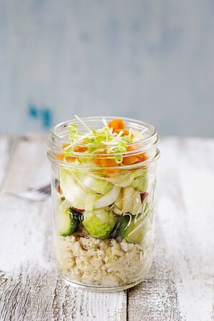 Salad in a glass with couscous, brussels sprouts, apple, chicory, carrot and lentil sprouts