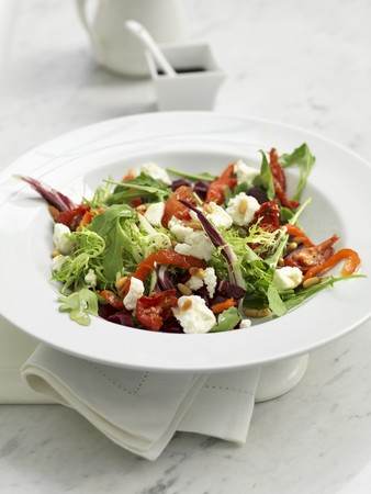 A mixed leaf salad with goats cheese, peppers and pine nuts LANG_EVOIMAGES