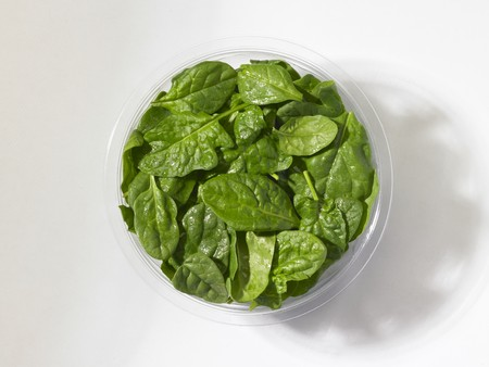 whiteness: Fresh baby spinach in a plastic bowl in front of a white background (seen from above)