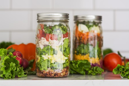 Two layered salads in glass jars with spinach, beans, cheese and eggs LANG_EVOIMAGES