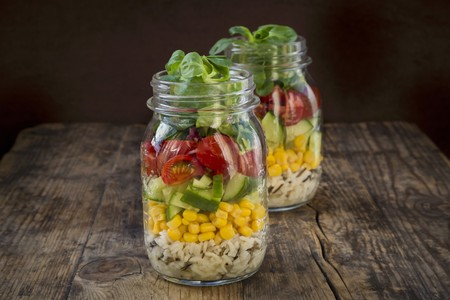 go inside: Rice salad in a glass jar with wild rice, sweetcorn, cucumber, tomato and lambs lettuce
