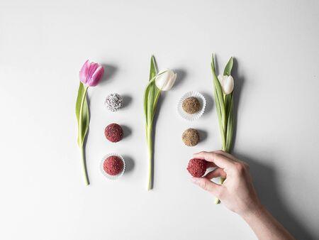 Various pralines arranged between tulips (seen from above) LANG_EVOIMAGES