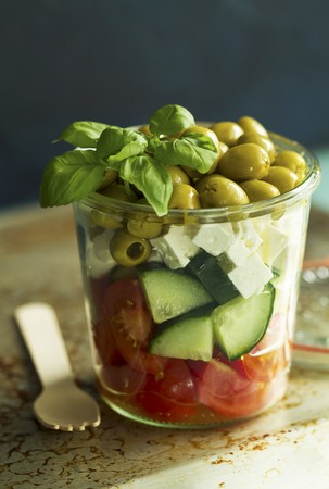 A salad of tomatoes, cucumbers, feta, green olives and basil in a glass