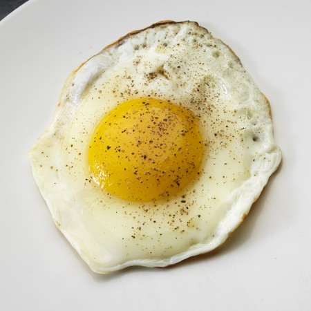 whiteness: Fried egg on white plate from above