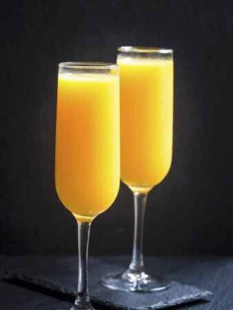 non alcoholic: Two glasses of freshly squeezed orange juice in front of a black background