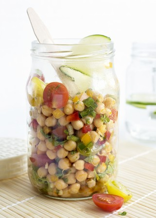 pimiento: A chickpea salad in a glass jar with tomatoes, peppers, red onions, spring onions, spices, limes, olive oil and fresh parsley LANG_EVOIMAGES