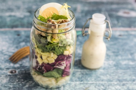 go inside: Orzo pasta with lambs lettuce, radicchio, endive, croutons, cheese, walnuts and eggs in a glass jar with dressing and a wooden fork LANG_EVOIMAGES