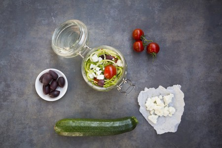 midday: Zoodles (zucchini noodles) in a glass jar with tomatoes, feta and olives LANG_EVOIMAGES