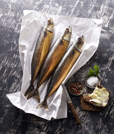 buttered: Three smoked mackerels on paper with salt and buttered bread