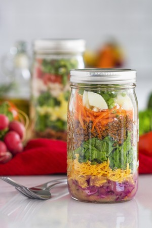 go inside: Layered salad in glass jars with spinach, carrots and cheese