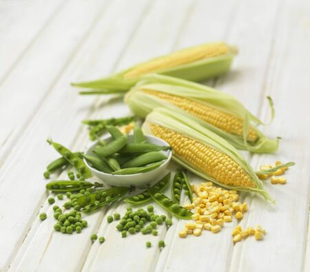 pea pod: Petit pois and corn on the cob on a wooden background