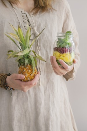 provenance: A woman in a linen dress holding a jar of fruit salad with mango, pomegranate seeds, lettuce and a fresh baby pineapple LANG_EVOIMAGES