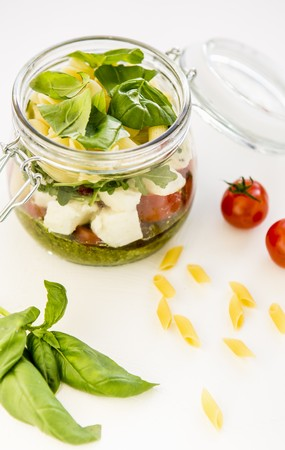 midday: Pasta salad with pesto, tomatoes, mozzarella, rocket and basil in a glass jar