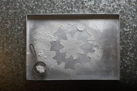 one sheet: An icing sugar snowflake on a baking tray (seen from above)