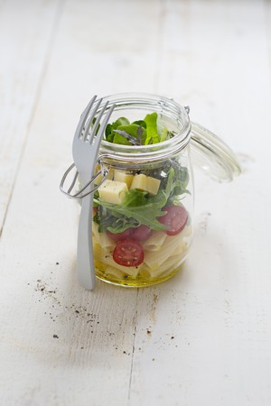 go inside: A pasta salad with cocktail tomatoes, rocket and mountain cheese in a glass jar with a fork