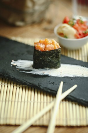 Single sushi with salmon tartare on a black plate LANG_EVOIMAGES