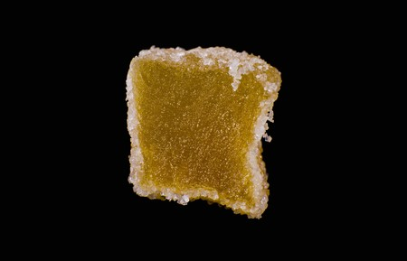A candied ginger cube against a black background