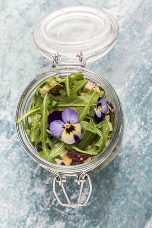 midday: Quinoa salad with lambs lettuce, radicchio, rocket, croutons, goats cheese and horned violets in a glass jar