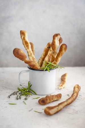gressins: Bâtonnets aux herbes dans une tasse en émail