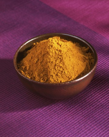 Curry powder in a small bowl on a pink tablecloth