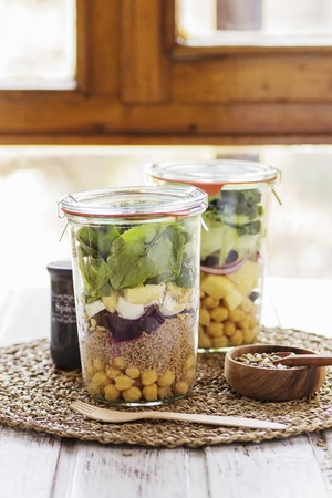 go inside: Two salads in jars prepared in a buffet service for a brunch with a mix of seeds for dressing
