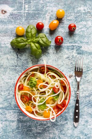 Zoodles (zucchini noodles) with tomatoes and basil LANG_EVOIMAGES