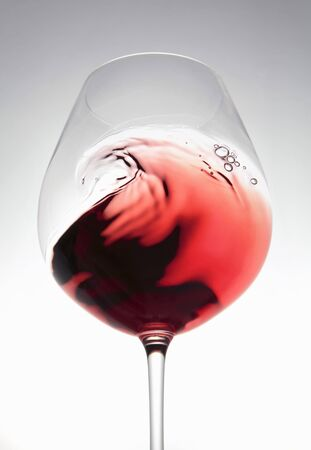 Red wine creating a wave in a glass
