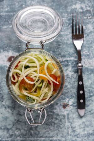 midday: Zoodles (zucchini noodles) in a glass jar with tomatoes and basil LANG_EVOIMAGES