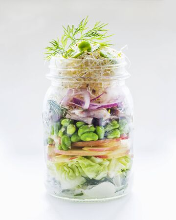 go inside: Vegetable salad with apple, edamame, herring and shoots in a glass jar