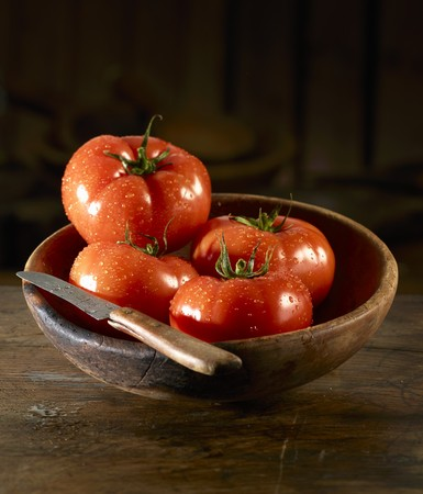 washed: Tomatoes with drops of water and a knife in a wooden bowl