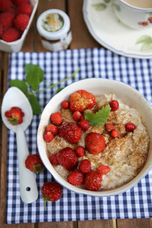 vintage furniture: Summer breakfast porridge with strawberries on a garden table