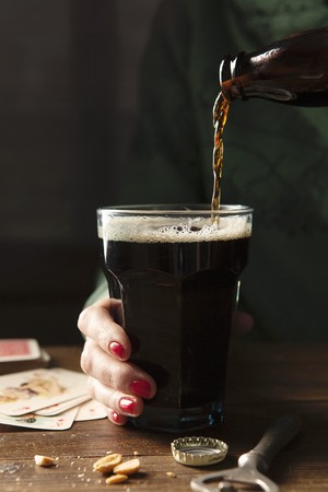 provenance: Bottle of Guinness being poured into a large glass being held by a hand with red nail varnish on a wooden table surrounds by the bottle top, bottle opener, nuts and playing cards