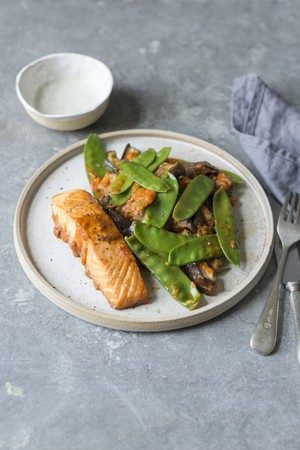 Roasted salmon fillet with roasted courgette, aubergine and green peas