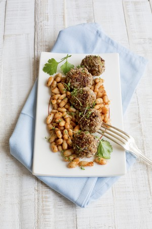 Meatballs on white beans with herbs