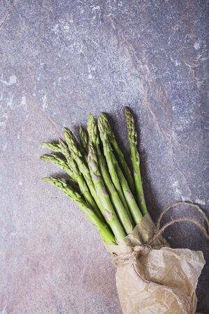 bunched: A bunch of fresh asparagus spears in a paper bag tied with string