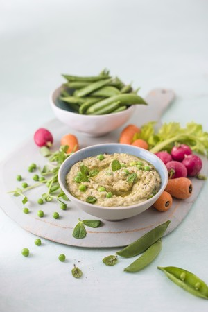 kitchen appliances: Houmous made of chickpeas, peas with mint and tahini, fresh vrgetables foe dipping on a side