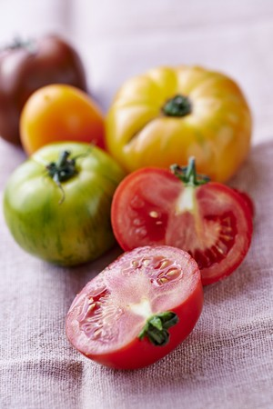 halved  half: Various coloured tomatoes on a linen cloth, one halved